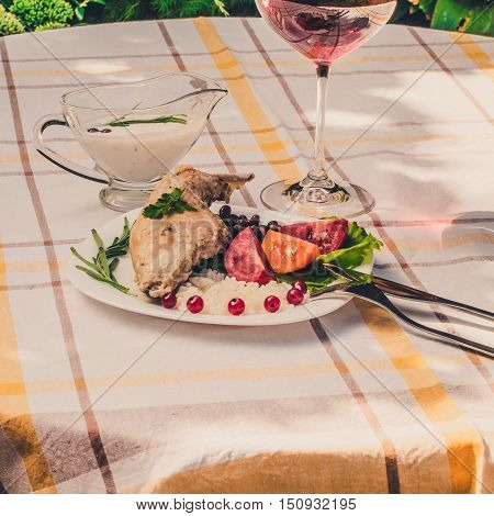 Gourmet roasted rabbit leg with rice and beans. White sauce and glass of red wine. Meal is served on white simple plate and checked table cloth with cutlery. Health and light meal good for diet.