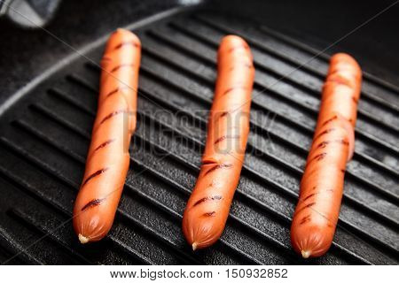 Close up of three hot Vienna sausages on the grill pan. Ingredients for making homemade hot dogs. Perfect lunch with easy dish. Fast food snack