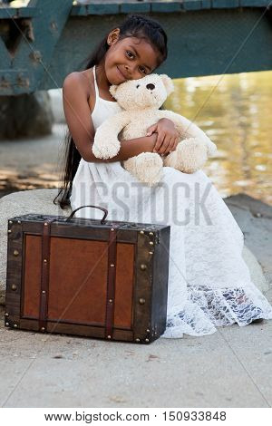 Smiling little girl with teddy bear in a pretty dress.