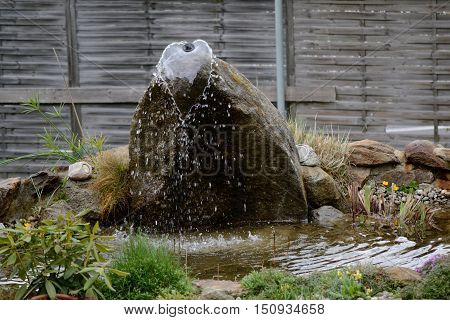 Fountain of stone in a pond embellish a garden
