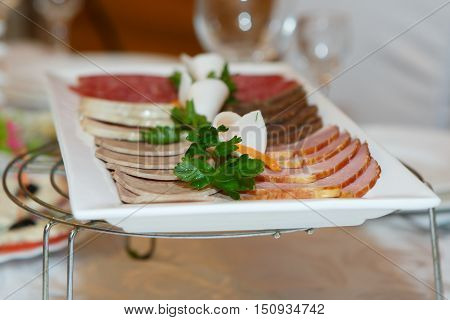 Dish of sliced ham and sausage. Deli meat served at the festive meal table. Appetizer of cooked meat products.