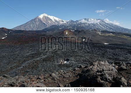Volcanic landscape of Kamchatka: summer view of cone of Ostry Tolbachik Volcano and cone of active Plosky Tolbachik Volcano on sunny day. Eurasia Russian Far East Kamchatka Peninsula Klyuchevskaya Group of Volcanoes.