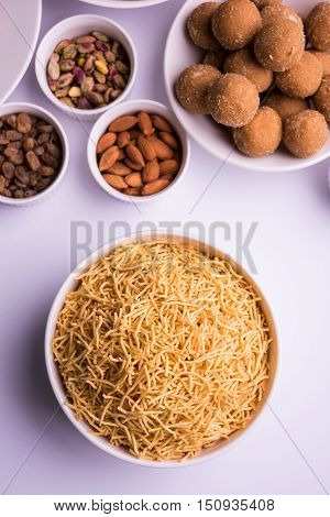 home made tasty Diwali food or Diwali snacks or Diwali sweets like rava laddu, chakli, sev, shankar pale and chivda or chiwada with dry fruits in white bowls, favourite indian diwali recipe