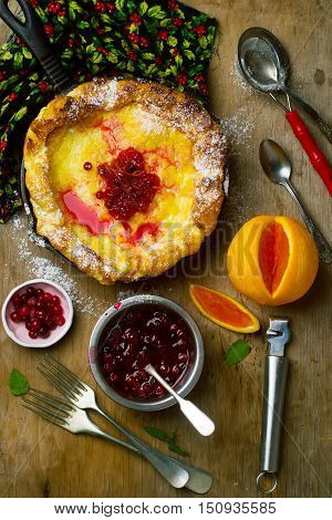 Dutch Baby with Cranberry Orange Compote. style rustic. selective focus