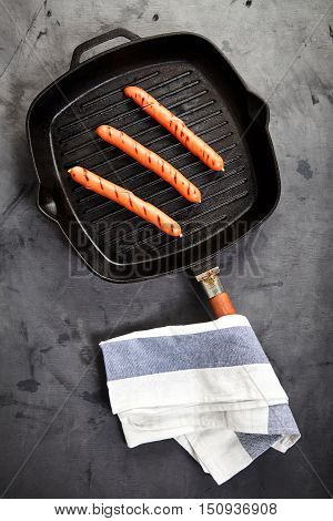 Top view of three hot Vienna sausages on the grill pan on a gray background with a kitchen towel nearby. Ingredients for making homemade hot dogs. Perfect lunch with easy dish. Fast food snack