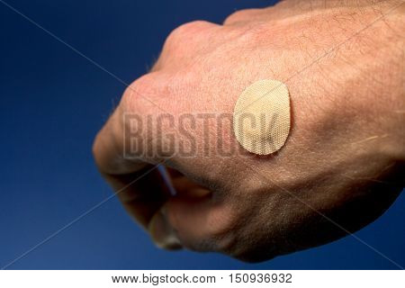 Bandage on a hand wound as a first aid on blue background