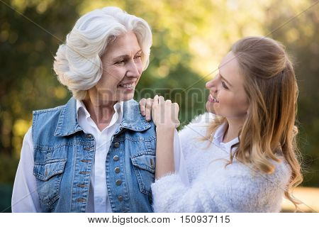 Thank you for everything. Joyful relaxed mother and daughter conversing and smiling while walking in the park.