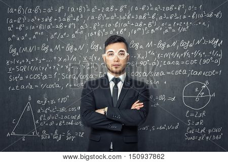Businessman standing on the background of blackboard with mathematical formulas. Science and education. Mathematics, algebra and geometry.