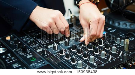Dj mixes the track in the nightclub at party. Shallow dof