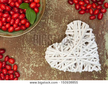 Ripe dogwood berries on wooden background and white colored heart shape