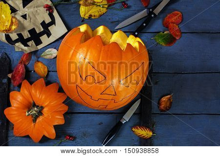 Preparing a carved pumpkin for halloween tinker autumn decoration on a blue rustic wooden table copy space selected focus