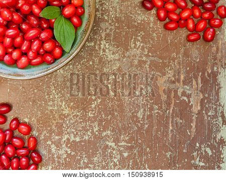 Ripe dogwood berries on wooden background with copyspace