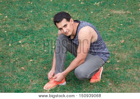 Young fitness man ties up bootlaces on his sport footwear outdoor