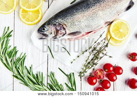 Ingrediets for baking trout: raw fresh rainbow trout on paper with cherry tomatoes, slices of lemon, sprigs of rosemary, thyme, pepper mill. Preparations for cooking delicious fish. White wood back