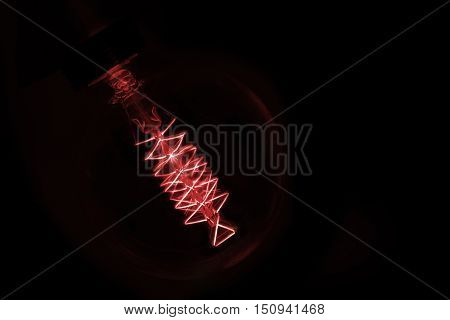 Close Up On Red  Light Bulb Glowing In Dark
