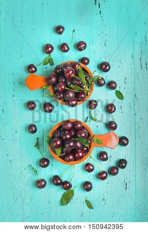Red ripe cherries in two brown bowl ceramic red cherries on wooden table green cherry leaves green wooden background. Top view.