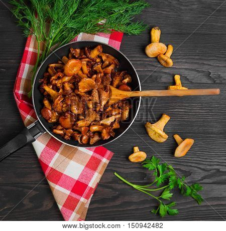 Chanterelle mushrooms fried in cast iron frying pan herbs for roasted chanterelles parsley dill cloth. Raw chanterelles on a dark brown background of wooden table. Top view.