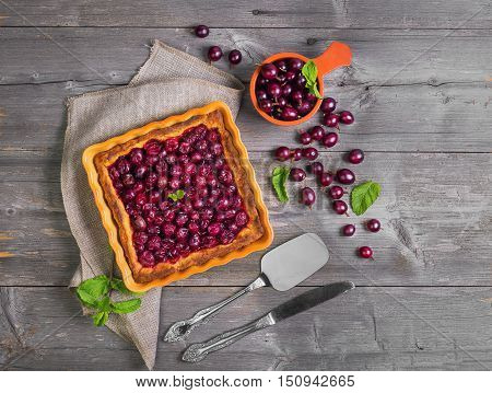 Fresh baked pie pastry with red berries of gooseberry in square ceramic form ripe berries of gooseberry for pie in bowl gooseberries on gray wooden table background mint scapula for pies