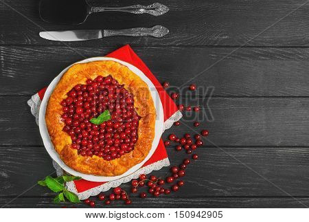 Open pies tart with berries red currant. Fresh red currant berries for Open pies tart mint red lace cloth. Dark black wooden background top view