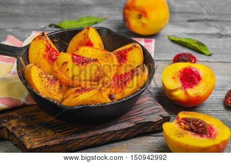 Baked peaches on a cast iron pan leaf cinnamon spices for baked peaches. Fresh red fruit yellow peaches for baking gray wooden background board.