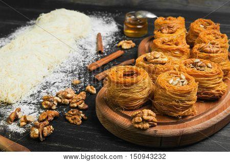 Cooking sweets turkish traditional ramadan pastry dessert kunafa kadaif baklava ingredients dough nuts walnuts peanuts sunflower seeds honey cinnamon dark black wood background
