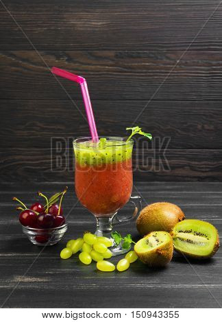 Fruit smoothie drink cocktail of kiwi cherries and grapes in glass. Ingredients fresh fruits for smoothie on dark wooden background cherry kiwi grapes Melissa leaves.