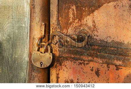 Old rusty padlock on rusty metal door wooden house