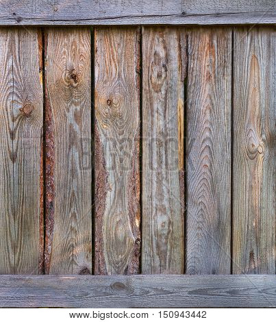 Old vintage wooden fence made of boards with slats nails. Wooden background with boards