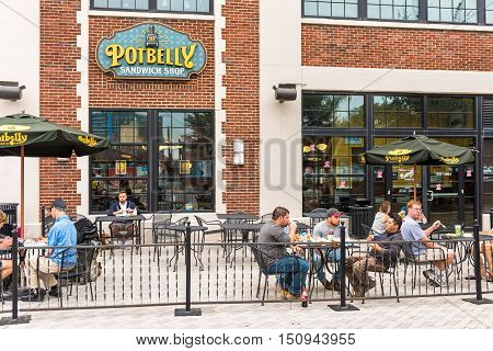 Washington DC, USA - September 24, 2016: Outside seating area of Potbelly fast food restaurant with sign and text and people eating lunch