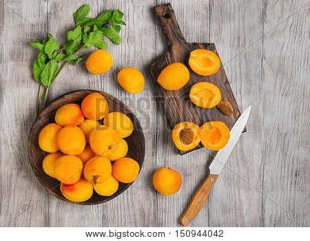 Fresh ripe apricots on wooden plate mint leaves fruits apricots on cutting board cut apricots in half. Light white rustic wood background. Top view.