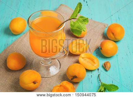 Glass with fresh apricot juice drink the whole fruit of apricot mint apricot halves and pits green wood background