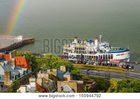 Quebec City, Canada - July 27, 2014: Rainbow in downtown with view of Saint Lawrence river and excursion boat with people