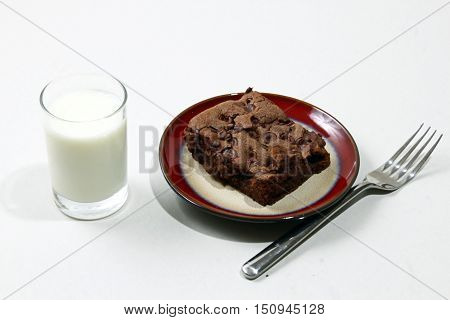 Chocolate brownies with chocolate chips on a plate with a glass of milk