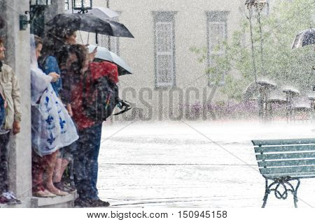Quebec City, Canada - July 27, 2014: A group of people hide from heavy rain under a building.