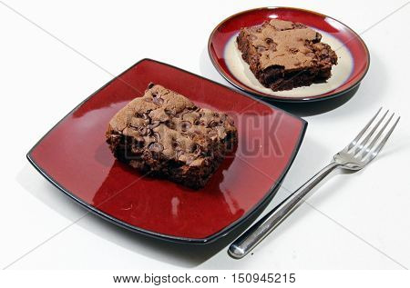 Chocolate brownies with chocolate chips on a plate with a glass of milk selective focus.