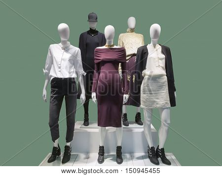 Five female mannequins dressed with fashionable modern clothes. Isolated on green background. No brand names or copyright objects.