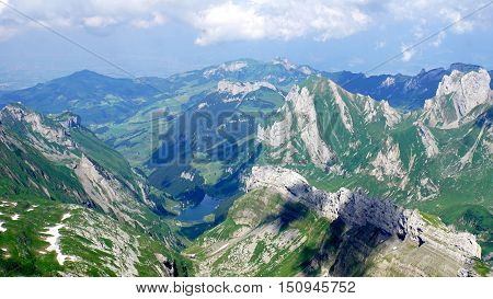 Mountain world in Switzerland, view from Säntis on the Alpstein-Massif with the Lake Seealp in the Appenzellerland, steep rocks and valleys,