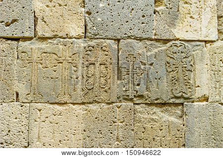 The stone plates of the wall of St Peter and Paul Cathedral with preserved old carved cross-stones (khachkars) Tatev Monastery Syunik Province Armenia.