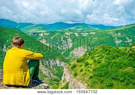 The man sits with tucked knees at the precipice ov Vorotan Canyon and listen to the mountain sounds Halidzor Syunik Province Armenia.