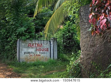 TANGALLE SRI LANKA ASIA - DECEMBER 12 2014: Sign for Ratna house bed and breakfast embedded in lush tropical vegetation on December 12 2014 in Tangalle Sri Lanka Asia.