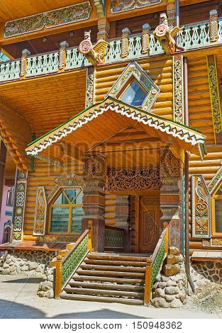 The wooden porch of the Tsar's Palace with the colorful carved patterns timbered columns and stairs traditional sculptures Izmailovsky Kremlin Moscow Russia.