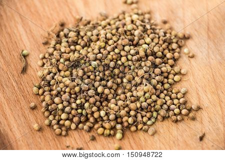 Handful of dryed coriander seeds on wood texture background