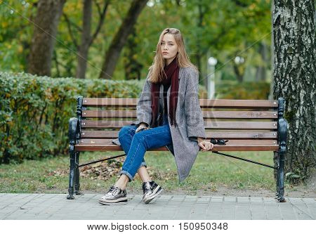 Beautiful Stylish Young Woman In A Warm Scarf Blue Jeans Trendy Shoes And Cozy Coat Sitting Alone On