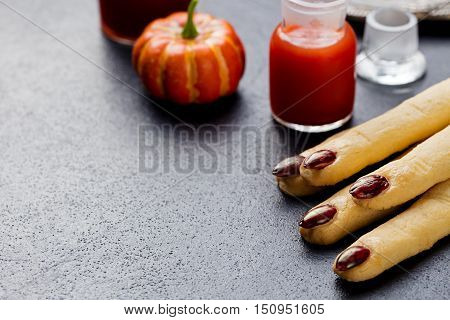 Cookies Witch's fingers with bloody cocktail for Halloween party celebration. Black stone background Copy space.