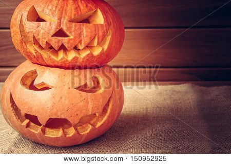 Halloween pumpkins pyramid with copyspace on wooden background with dark edges