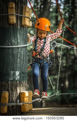 sports happy kid climbs through the ropes, the beautiful girl in the outfit climbing fun in the forest on ropes and different obstacles