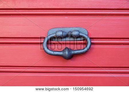 Old metal door knocker on a wooden door