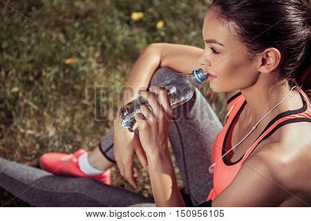Restore energy. Beautiful slim young girl drinking water from a bottle after doing morning exercises wearing sportswear and headphones.