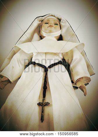 low angle view of a catholic nun doll with rosary beads