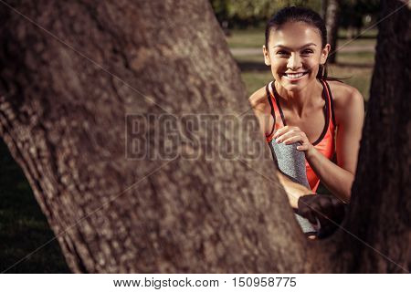 Much fun and energy. Laughing beautiful young girl wearing sportswear and posing in the park behind the tree after having morning training.